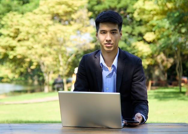 Młody biznesmen azjatyckich siedzi w ogrodzie do pracy