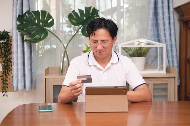 Młody biznesmen azjatyckich w ubranie siedzi z komputerem typu tablet