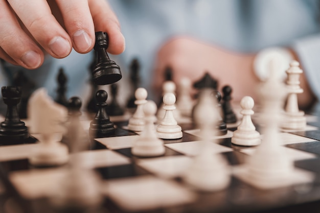 Młody biznesmen bawić się szachy w biurze