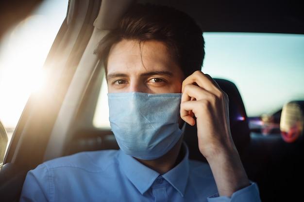 Młody biznesmen bierze taksówkę i wygląda przez okno samochodu, dopasowując sterylną maskę medyczną. pojęcie dystansu społecznego.