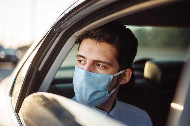 Młody biznesmen bierze taksówkę i wygląda przez okno samochodu w sterylnej masce medycznej. pojęcie dystansu społecznego.