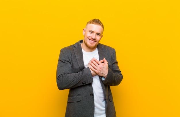 Młody biznesmen blond czuje się romantyczny, szczęśliwy i zakochany, uśmiecha się radośnie i trzyma ręce blisko serca