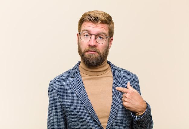 Młody biznesmen blond czuje się zdezorientowany, zdziwiony i niepewny, wskazując na siebie, zastanawiając się i pytając, kto, ja?