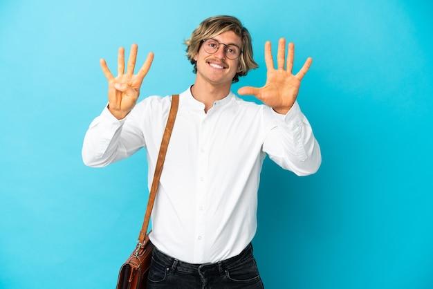 Młody biznesmen blondynka na białym tle na niebieskim tle, licząc dziewięć palcami