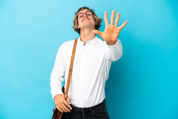 Młody biznesmen blondynka na białym tle na niebieskim tle, licząc pięć palcami