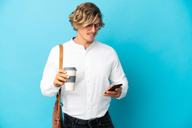Młody biznesmen blondynka na białym tle na niebiesko trzymając kawę na wynos i telefon komórkowy