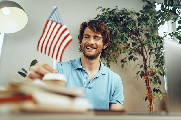 Młody biznesmen brodaty siedzi przy stole z laptopem i amerykańską flagą