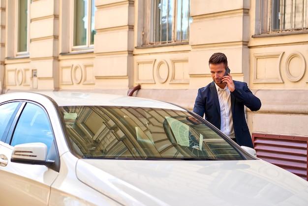 Młody biznesmen chodzi do jego samochodu i opowiada na telefonie