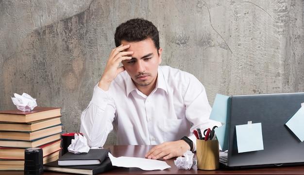 Młody biznesmen ciężko myśli przy biurku.