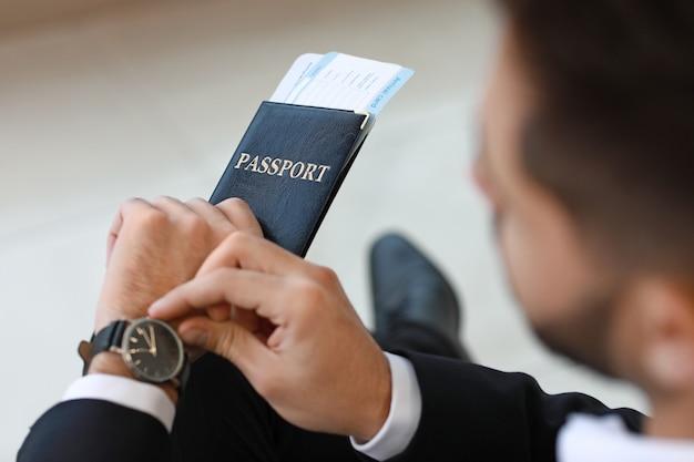 Młody biznesmen czeka na lot na lotnisku, zbliżenie