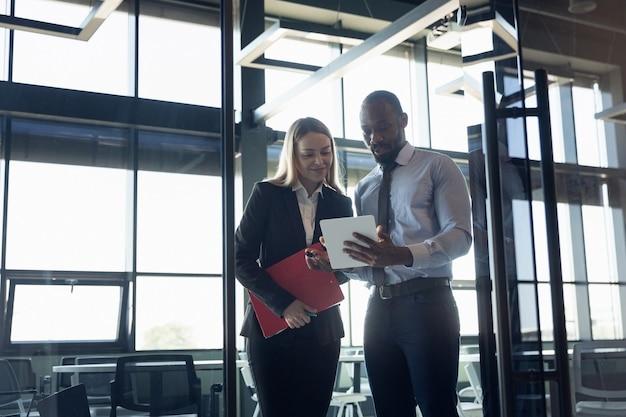 Młody biznesmen czeka na wyjazd na lotnisko, podróż służbowa, biznesowy styl życia. mężczyzna i kobieta z gadżetami przed wyjazdem na wakacje, rejestracja. wspólna praca w specjalnej strefie oczekiwania.