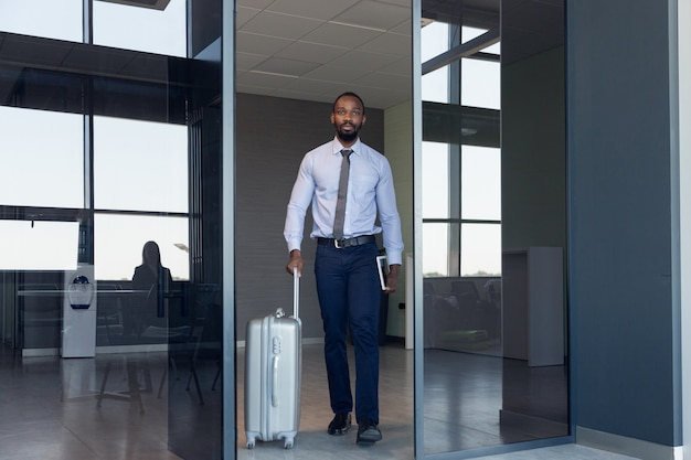 Młody biznesmen czeka na wyjazd na lotnisko, podróż służbowa, biznesowy styl życia.