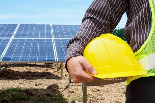 Młody biznesmen człowiek inżynier trzymać żółty kask na tle placu budowy elektrowni paneli słonecznych
