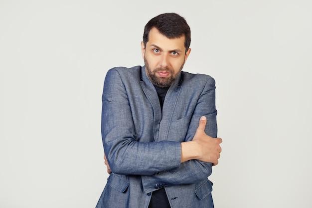 Młody biznesmen człowiek z brodą w kurtce, trzęsąc się i marznąc z zimowego mrozu ze smutnym i zszokowanym wyrazem twarzy.