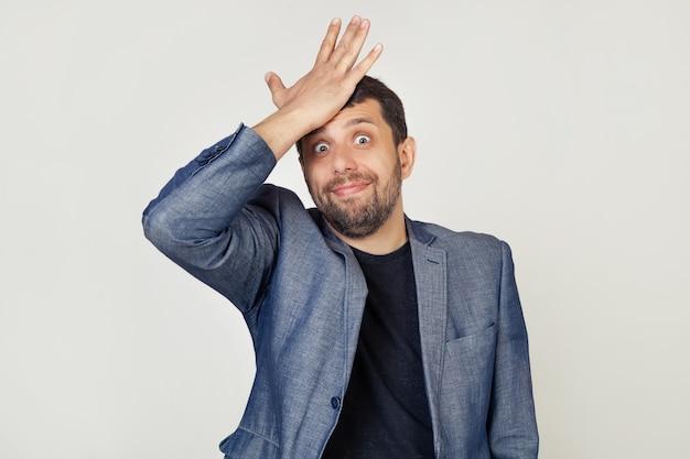 Młody biznesmen człowiek z brodą w kurtce, z wyrazem frustracji i nieporozumień. zaskoczony, kładąc rękę na głowie za błąd.