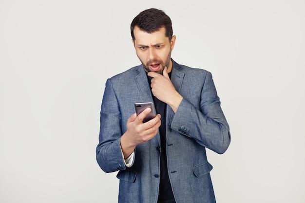 Młody biznesmen człowiek z brodą w kurtce za pomocą smartfona przestraszony zszokowany zdziwioną miną
