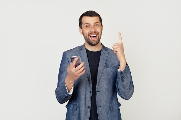 Młody biznesmen człowiek z brodą w kurtce za pomocą smartfona zaskoczony pomysłem lub pytaniem