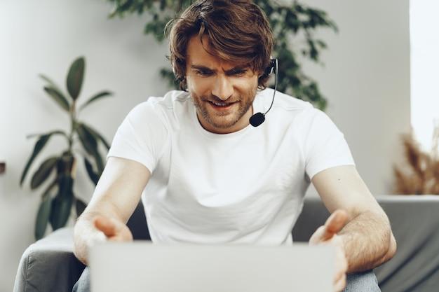 Młody biznesmen człowiek z zestawu słuchawkowego pracuje na laptopie z domu