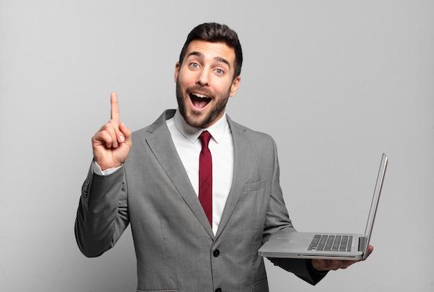 Młody biznesmen czując się jak szczęśliwy i podekscytowany geniusz po zrealizowaniu pomysłu, radośnie podnosząc palec, eureka! i trzymam laptopa
