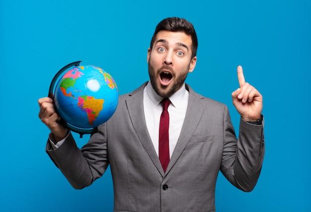 Młody biznesmen czując się jak szczęśliwy i podekscytowany geniusz po zrealizowaniu pomysłu, radośnie podnosząc palec, eureka! trzyma światową mapę globu
