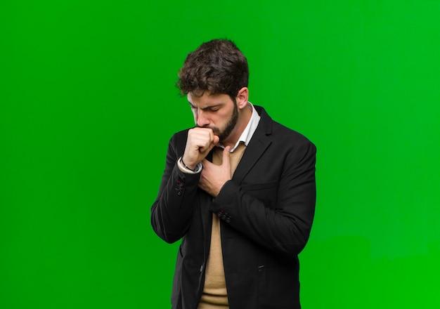 Młody biznesmen czuje się chory z bólem gardła i objawami grypy, kaszel z usta pokryte