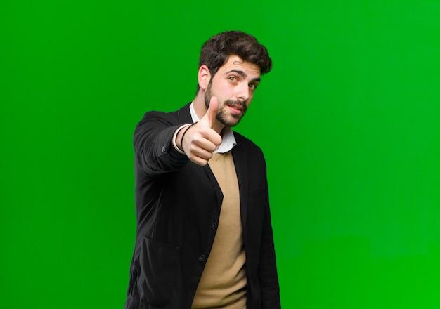 Młody biznesmen czuje się dumny, beztroski, pewny siebie i szczęśliwy, uśmiechając się pozytywnie z kciuki do góry zielony