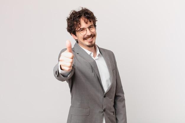 Młody biznesmen czuje się dumny, uśmiecha się pozytywnie z kciukami w górę