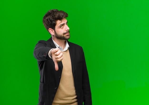 Młody biznesmen czuje się krzyżowo, zły, zirytowany, rozczarowany lub niezadowolony, pokazując kciuk w dół z poważnym spojrzeniem na zielono