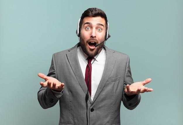 Młody biznesmen czuje się niezwykle zszokowany i zaskoczony, niespokojny i spanikowany, ma zestresowany i przerażony wyraz twarzy