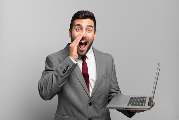 Młody biznesmen czuje się szczęśliwy, podekscytowany i pozytywnie nastawiony, wydając wielki okrzyk z rękami przy ustach, wołając i trzymając laptopa