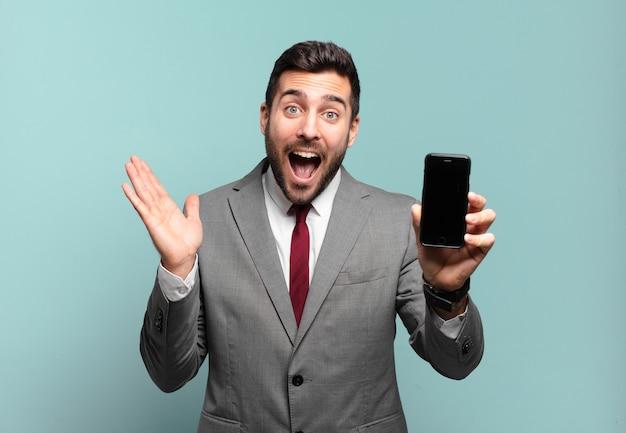 Młody biznesmen czuje się szczęśliwy, podekscytowany, zaskoczony lub zszokowany, uśmiecha się i zdumiony czymś niewiarygodnym i pokazuje ekran swojego telefonu