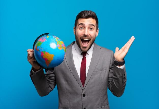 Młody biznesmen czuje się szczęśliwy, podekscytowany, zaskoczony lub zszokowany, uśmiechnięty i zdumiony czymś niewiarygodnym, trzymającym mapę świata