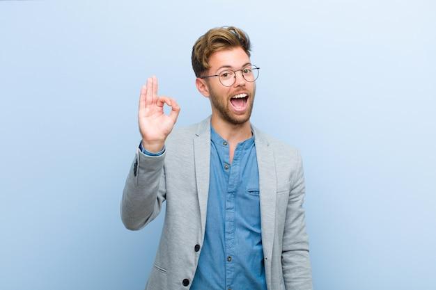 Młody biznesmen czuje się udany i zadowolony, uśmiechając się z szeroko otwartymi ustami, co dobrze znak ręką