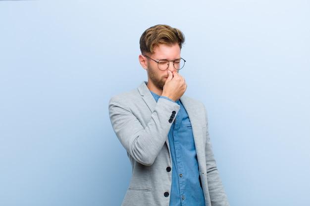Młody biznesmen czuje się zdegustowany, trzymając nos, aby uniknąć wąchania nieprzyjemnego i nieprzyjemnego smrodu na niebieskim tle