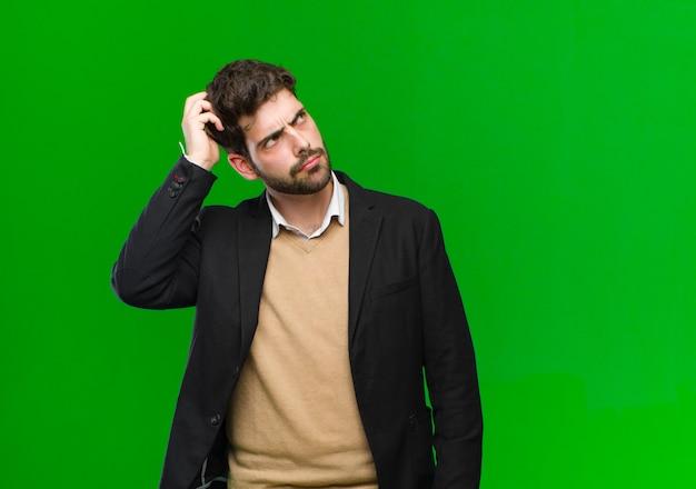 Młody biznesmen czuje się zdziwiony i zdezorientowany, drapie się po głowie i patrzy w bok na zielono