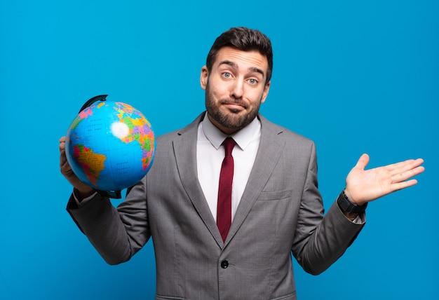 Młody biznesmen czuje się zdziwiony i zdezorientowany, wątpi, rozważa lub wybiera różne opcje z zabawnym wyrazem twarzy, trzymając mapę świata