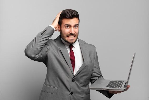 Młody biznesmen czuje się zestresowany, zmartwiony, niespokojny lub przestraszony, z rękami na głowie, panikujący z powodu błędu i trzymający laptopa