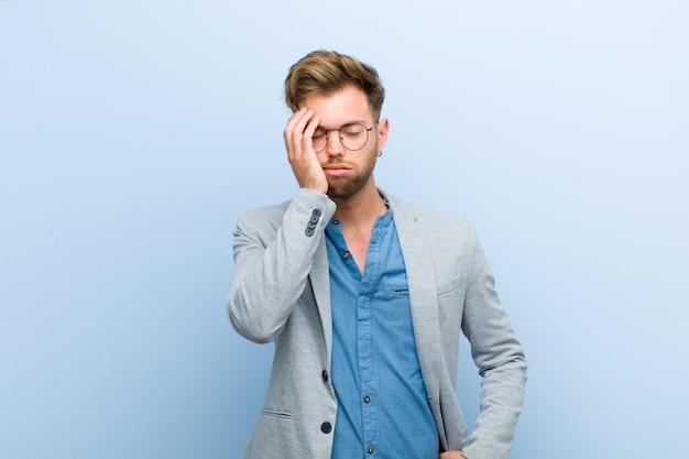 Młody biznesmen czuje się znudzony, sfrustrowany i senny po męczącym, nudnym i żmudnym zadaniu, trzymając twarz ręką