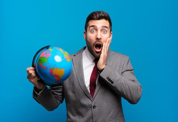 Młody biznesmen czuje się zszokowany i przestraszony, wygląda na przerażonego z otwartymi ustami i rękami na policzkach, trzymając mapę świata