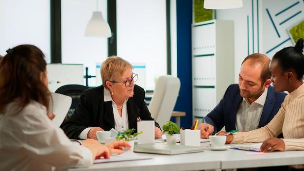 Młody biznesmen czyta dokumenty, podpisuje swoje i konsultant pozdrawia międzynarodowego klienta z uściskiem dłoni po zaplanowaniu umowy partnerskiej. dyrektor wykonawczy spotykający się z udziałowcami w biurze start up