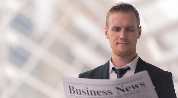 Młody biznesmen czyta wiadomości prasowe w ranku.