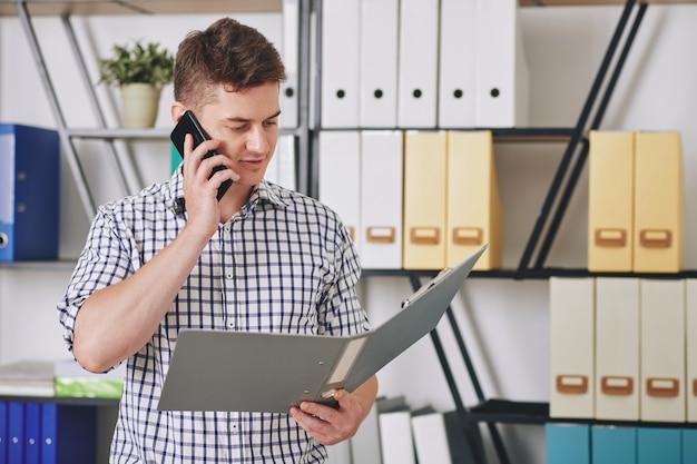 Młody biznesmen czytanie raportu w otwartym folderze i rozmawia telefon z kolegą