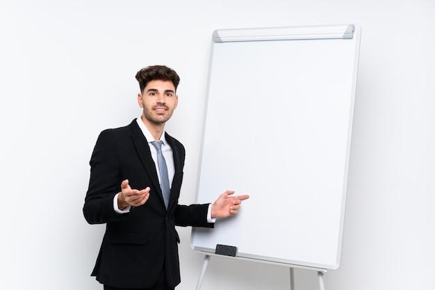 Młody biznesmen daje prezentaci na białej desce daje prezentaci