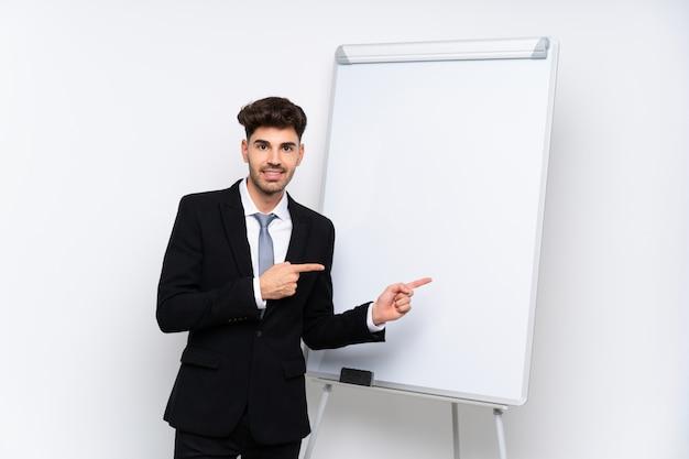 Młody biznesmen daje prezentaci na białej desce zaskakującej i wskazuje stronę