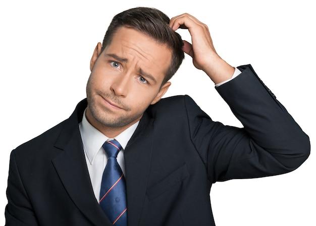 Młody biznesmen drapiący się po głowie, trudna decyzja