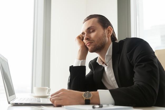 Młody biznesmen drzemał przed laptopem przy pracą.