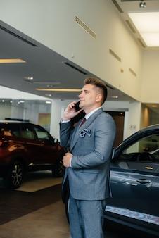 Młody biznesmen dzwoni po zakupie nowego samochodu