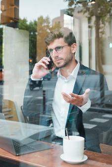 Młody biznesmen gestykuluje opowiadać na mądrze telefonie w kawiarni