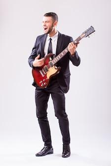 Młody biznesmen gra na gitarze na białym tle na białej ścianie