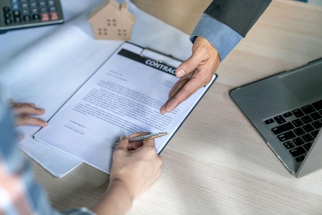 Młody biznesmen i nabywca domu wspólnie osiągnęli docelowe środki i podpisali umowę sprzedaży nieruchomości
